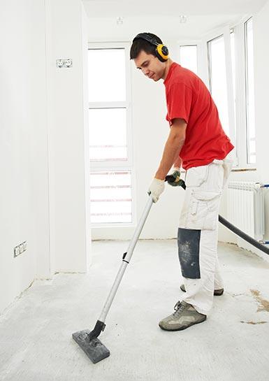Trabajador de empresa de limpiezas encargándose de limpiar después de una reforma integral de un piso.