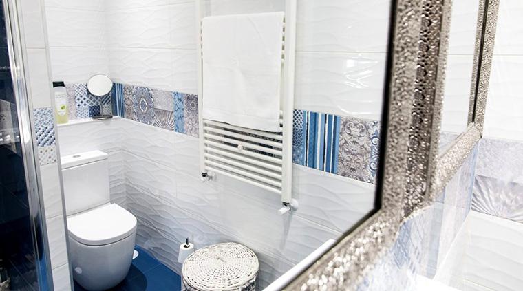 Las superficies brillantes ayudan a dar luz a un baño sin ventilación en la reforma de un piso oscuro.